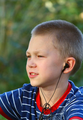 Teenager listens to music in headphones with a player