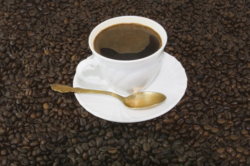 White coffee cup on brown roasted beans