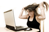 A woman expresses fury whilst looking at her laptop. poster