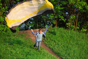 boy with parachute running from hill