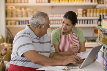Hispanic business owners using laptop
