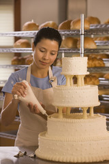 Hispanic woman decorating wedding cake