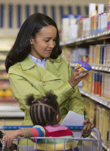 Woman with daughter in shopping cart at grocery store