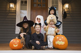 Children in Halloween costumes with pumpkins