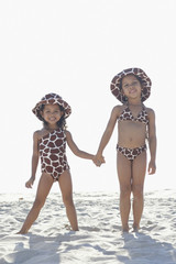 Young mixed race girls holding hands at beach