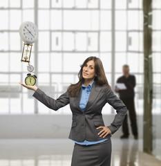 Businesswoman balancing clocks in hand