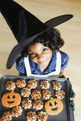 African girl holding Halloween cookies