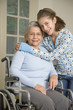 Granddaughter hugging grandmother in wheelchair