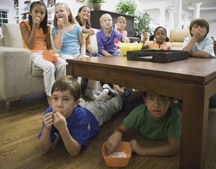 Children eating popcorn in livingroom