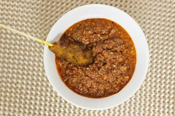 Asian cuisine - Stick of satay dipped in peanut sauce