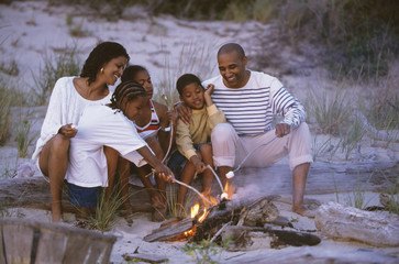 African family roasting marshmallows on beach
