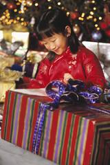 Asian girl opening gift on Christmas