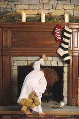 Child in pajamas looking up chimney