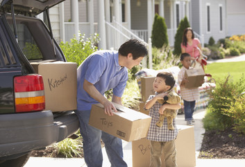 Asian family packing moving boxes into car