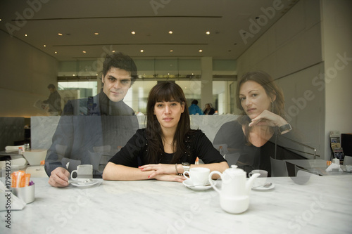 Woman at cafe with ghosted figures
