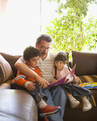 Grandfather reading to grandchildren on sofa