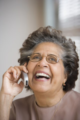 Senior Hispanic woman smiling and using cell phone