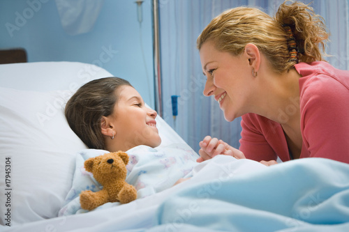 Mother smiling at daughter in hospital bed