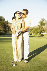 Hispanic man helping wife with golf swing