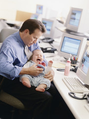 Businessman holding crying baby at desk