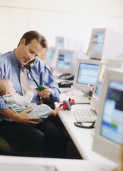 Businessman holding baby at desk