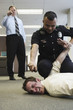 Police officer holding beat up businessman on floor in office