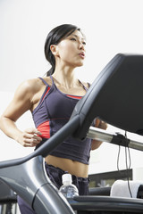 Asian woman running on treadmill