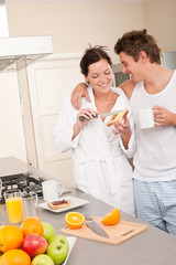 Happy couple having breakfast in the kitchen