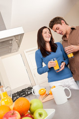 Young man and woman drinking orange juice