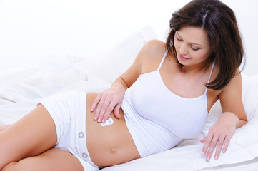 Pregnant young woman applying  cream on  belly