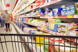 blurred shopping people with supermarket cooling shelf