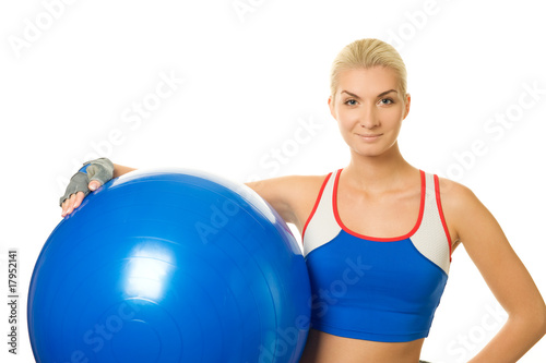 Happy trainer holding a fitness ball