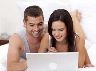 Couple in bed using a laptop