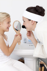 Little girl holding a mirror and mother putting makeup