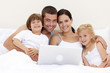 Portrait of family using a laptop in bed
