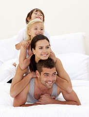 Family climbing on top of each other in bed