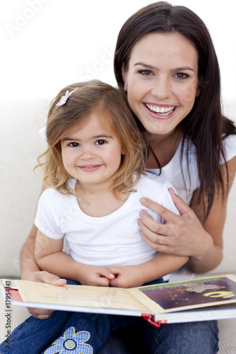 Smiling mother and daughter reading a book