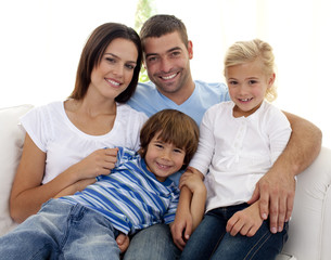 Smiling young family sitting on sofa
