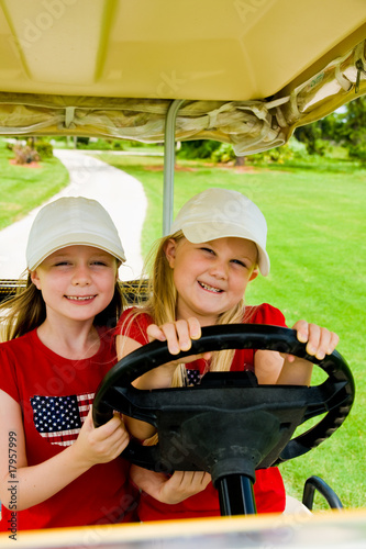 little sisters driving a golf cart