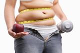 fat woman with unzup jeans holding apple and weight on each hand