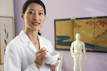 Asian female doctor using mortal and pestle