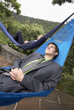 Hispanic businessmen sleeping in hammocks outdoors