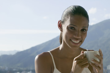 African woman drinking coffee with mountains in background