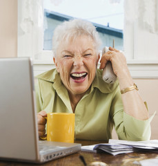Senior woman paying bills and laughing