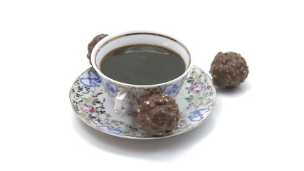 Cup of coffee rotating with chocolate candies