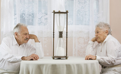 Senior couple staring at hourglass