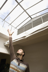 Man with arm raised up towards skylight