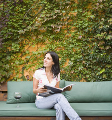 Woman drinking and reading on patio bench