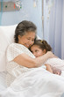Hispanic girl hugging grandmother in hospital bed