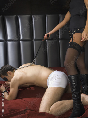 Dominatrix holding leash around man's neck